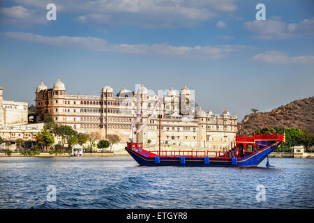 Boat on the Pichola lake with City Palace view at blue sky in Udaipur, Rajasthan, India - Stock Photo