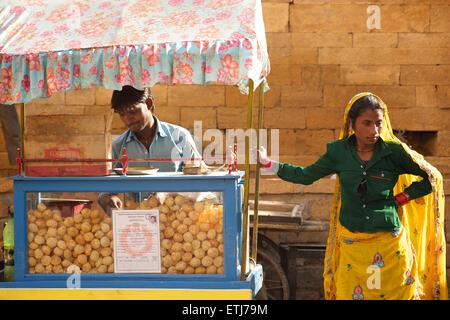 Indian street vendor and woman in sari. Jaisalmer, Rajasthan, India - Stock Photo