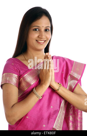 Portrait of traditional Indian woman greeting 'NAMASTE' - Stock Photo