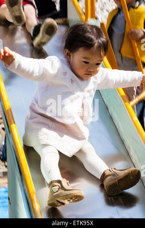 Close up of Japanese, Asian child, girl, 2-3 year old, sliding down playground slide with hands held outstretched. - Stock Photo