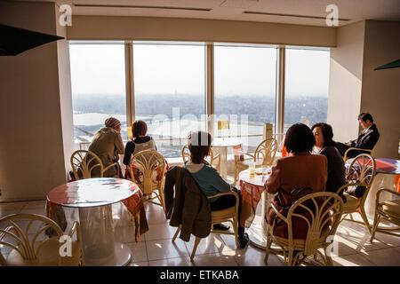 Japan, Osaka. Umeda Sky Building. Coffee shop, people seated chatting and enjoying the overhead views of Osaka city - Stock Photo