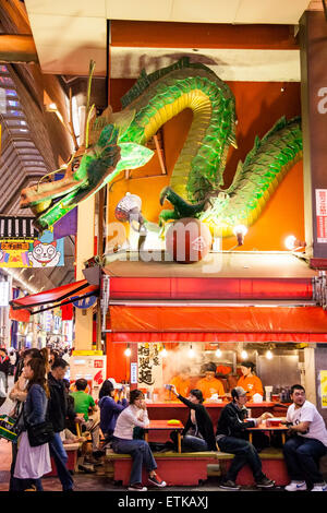 Japan, Osaka, Dotonbori. Kinryu ramen noodle restaurant, night, large dragon sign above crowded front of restaurant. - Stock Photo
