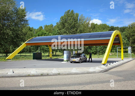 An electric car being charged at a Fastned electric vehicle charging station at a motorway service area in the Netherlands. - Stock Photo
