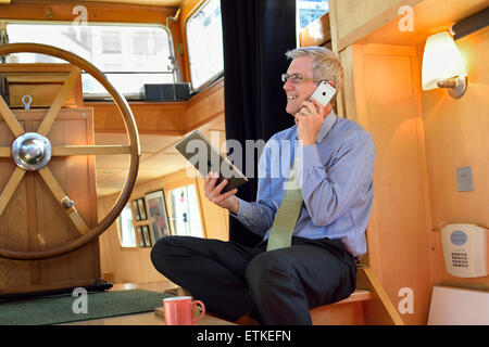 Relaxed mature businessman in houseboat office holding his iPad air tablet computer screen and using his iPhone - Stock Photo