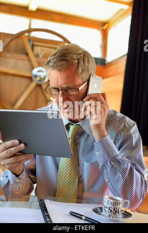 Serious mature man working in houseboat office using iPad tablet computer and iPhone 6 concentrates on the screen - Stock Photo