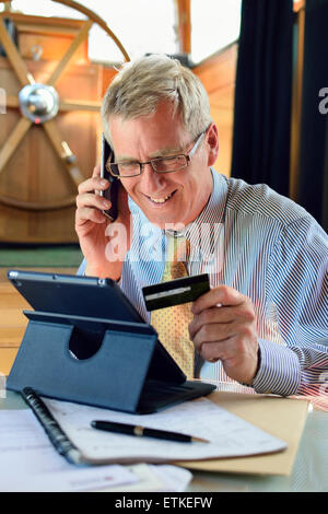 On line credit card mature businessman in his barge houseboat office making a card transaction on line using iPad - Stock Photo