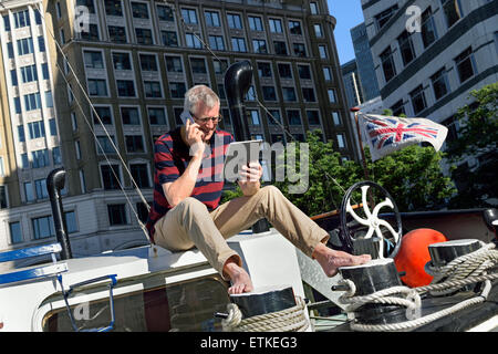 Relaxed mature man sitting outside on his boat talking on iPhone 6 looking at his iPad, offices behind Canary Wharf - Stock Photo