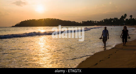 Mirissa Beach, tourist couple taking a romantic walk under a palm tree at sunset, South Coast of Sri Lanka, Southern - Stock Photo