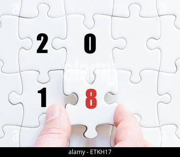 Hand of a business man completing the puzzle with the last missing piece. Concept image of puzzle board with year - Stock Photo