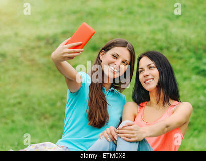 two happy women friends laughing and sharing social media pictures in a smart phone on picnic at the park, lifestyle - Stock Photo