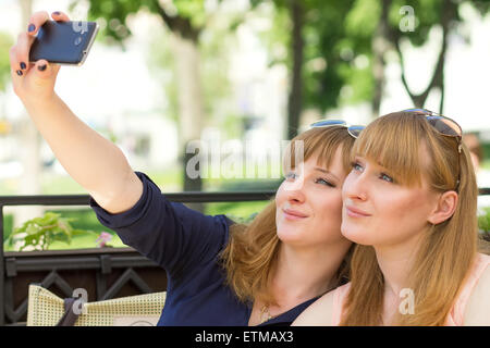Two twins girls taking selfie in restaurant at sunny summer day. Young pretty sisters on terrace of cafe - Stock Photo