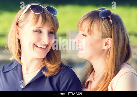 Young twins girls having fun laughing in summer park. Pretty students sister with sunglasses talking each other. - Stock Photo