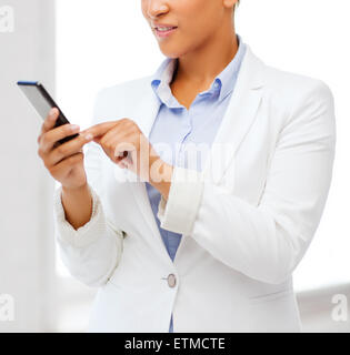 african businesswoman with smartphone in office - Stock Photo