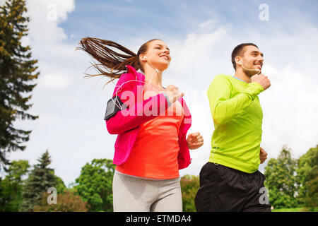 smiling couple with earphones running outdoors - Stock Photo