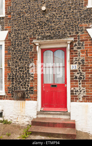 old Victorian entrance of Kentish flint knapped stone wall in terrace contrasts with red door and steps - Stock Photo