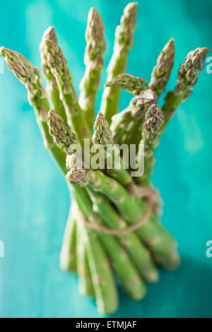 bunch of fresh asparagus on turquoise background - Stock Photo