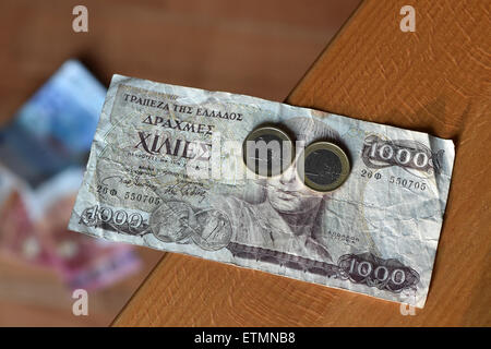 Berlin, Germany. 14th June, 2015. ILLUSTRATION - Two one euro coins cover the eyes of Greek god Apollo on a 1000 Greek drachma bill in Berlin, Germany, 14 June 2015. Photo: Jens Kalaene/dpa/Alamy Live News