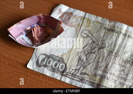 Berlin, Germany. 14th June, 2015. ILLUSTRATION - A ten euro bill which has been folded into a boat lies on a 1000 Greek drachma bill in Berlin, Germany, 14 June 2015. Photo: Jens Kalaene/dpa/Alamy Live News