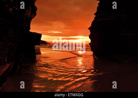 Spain, Galicia: Scenic sundown  between rocks at beach Praia As Catedrais - Stock Photo
