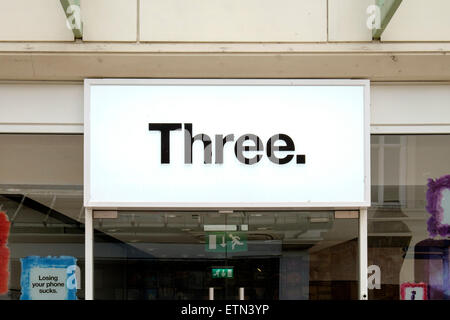 Three mobile phone shop name and logo sign above entrance on UK high street - Stock Photo