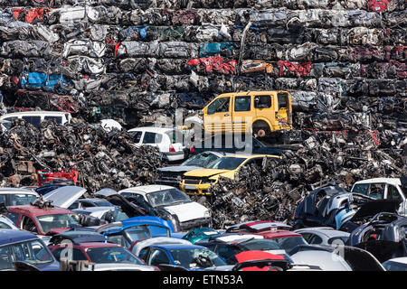 Stacked wrecked cars going to be shredded in a recycling plant - Stock Photo
