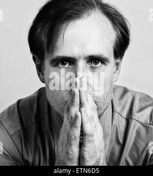 Close-up portrait of a mid adult man with his hands in front of his mouth - Stock Photo