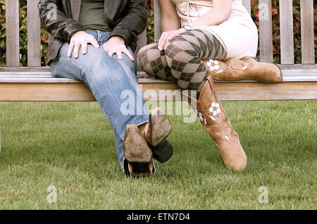 Low section of a couple wearing cowboy boots sitting on a bench - Stock Photo