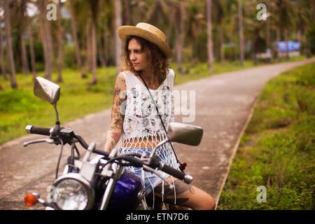 Edgy tattooed woman sitting on a motorbike - Stock Photo
