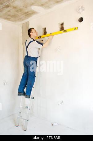 Workman on a ladder using a spirit level - Stock Photo