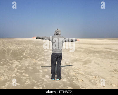 Rear view of a man with outstretched arms on a beach, Denmark - Stock Photo