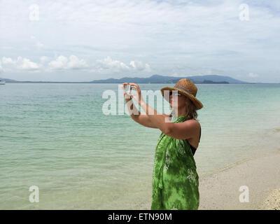 Woman standing on beach taking a photo, Phuket, Thailand
