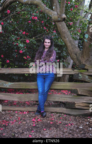 Portrait of a woman leaning against a wooden fence, Vancouver, Canada - Stock Photo