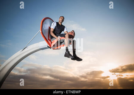 Portrait of a young man sitting in a basketball hoop in a park, Los Angeles, California, USA
