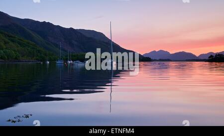 A colour image of the sunset on a still loch leven taken from ballachulish - Stock Photo