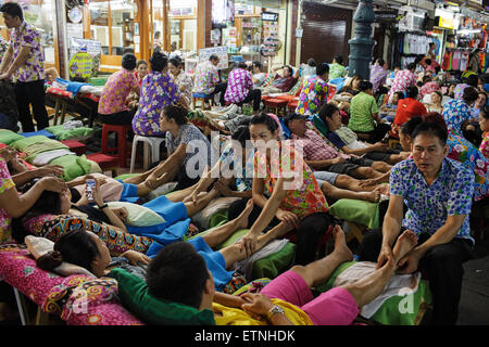 Foreign tourists having massage at night on Khao San road in Bangkok, Thailand. - Stock Photo