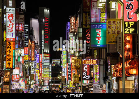 Neons and bright lights in one of streets of Kabukicho entertainment and red light district at night in Shinjuku, - Stock Photo