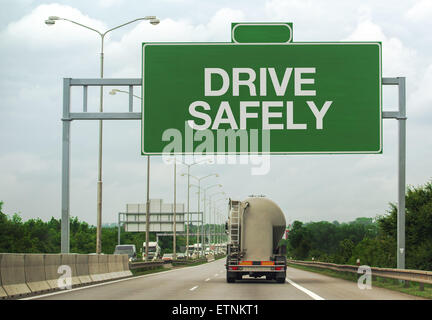 Fuel Tanker Truck on Highway Road Passing by Drive Safely Sign as a Reminder for Safety in Traffic - Stock Photo