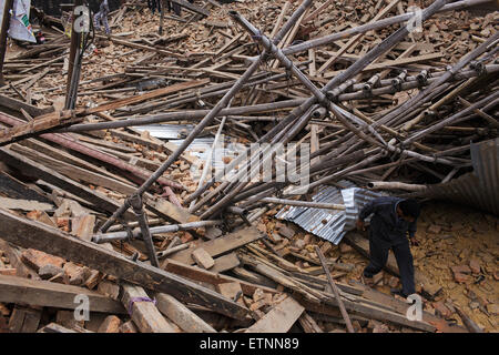 A man walks through rubble of two collapsed temples at Durbar Square. Rescue operations at Durbar Square in Kathmandu, - Stock Photo
