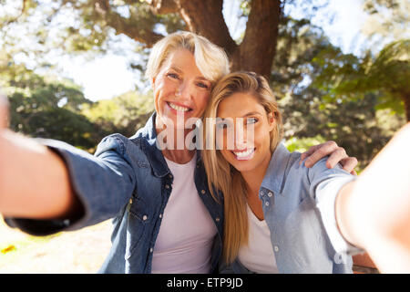 happy senior woman and daughter taking selfie together - Stock Photo