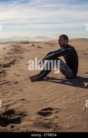 Kite surfer in Wet suit sitting on beach, thoughtful, wistful, beach, costa Brava, girona - Stock Photo