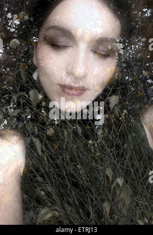 a montage of a portrait of a womans face with flowers and textures - Stock Photo