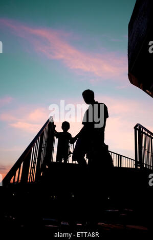 Silhouetted man and child walking down stairs in sunset - Stock Photo