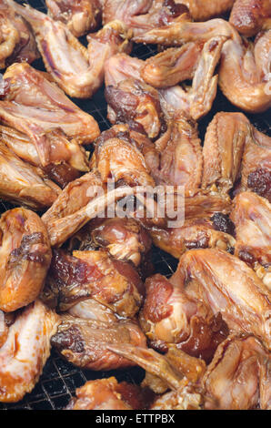 Raw honey chicken wings on BBQ grill - Stock Photo