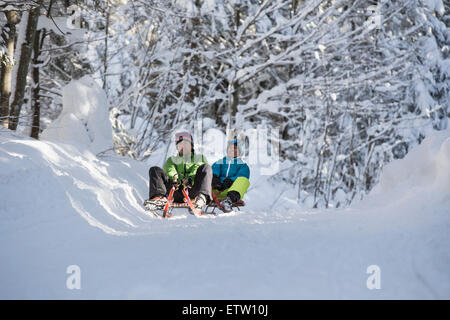 Germany, Bavaria, Inzell, couple having fun on sledges in snow-covered landscape - Stock Photo