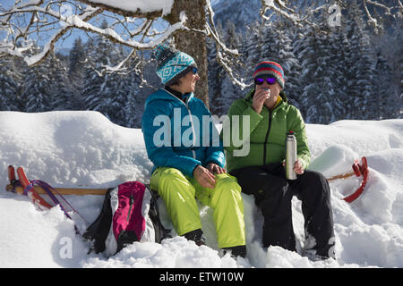 Germany, Bavaria, Inzell, couple having a rest snow-covered landscape - Stock Photo