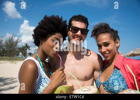 Three Latin people on the beach - Stock Photo