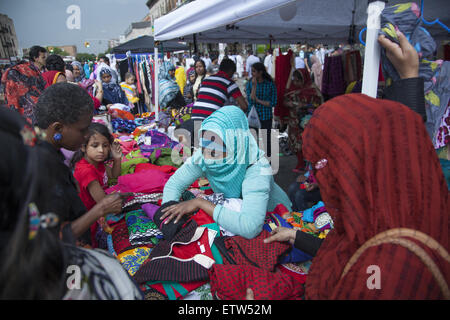 Bangladeshi women shop for clothes at a street fair in the 'Little Bangladesh' neighborhood of Brooklyn, NY. - Stock Photo