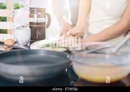 Couple preparing scrambled eggs together in the kitchen - Stock Photo