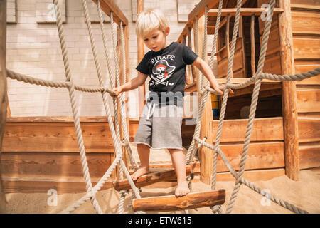 Little boy walking along hanging bridge of wooden ship on playground - Stock Photo