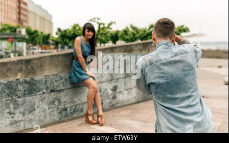 Spain, Gijon, young man taking pictures of his girlfriend with an old camera - Stock Photo